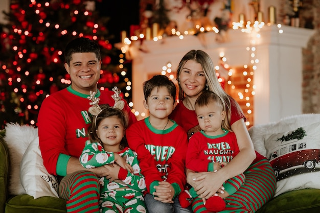 クリスマスの設定に対してソファに一緒に座っているクリスマスパジャマの5人の大きな若い家族。