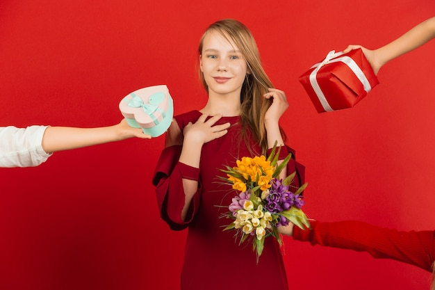 The biggest choice. valentine's day celebration. happy, cute caucasian girl isolated on red studio background. concept of human emotions, facial expression, love, relations, romantic holidays.
