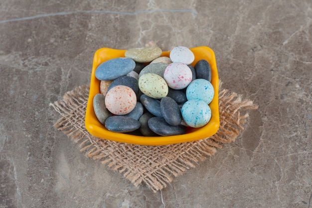 Caramelle di pietra multicolori bight in ciotola arancione.