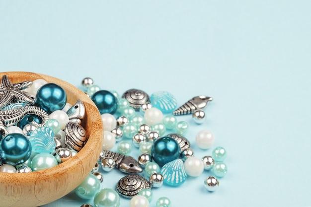 宝石類。ビーズからネックレスを作る。青い背景