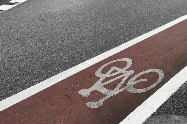 Bike lane asphalt texture, bicycle sign on street.