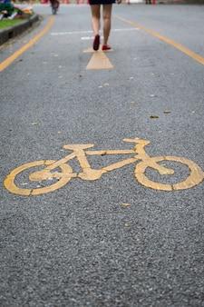 자전거 차선 및 노란색 자전거 기호, 공공 공원 정원 배경에서 자전거 골목