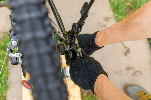 Bike mechanic man repairs bicycle in bicycle repair shop outdoor hand of cyclist bicyclist examines ...