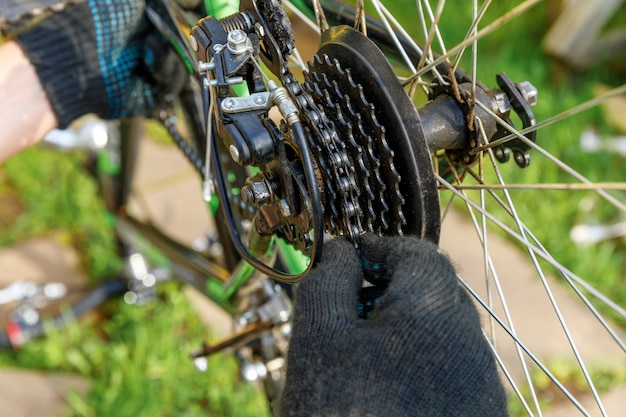自転車整備士が屋外の自転車修理店で自転車を修理します。サイクリストの手自転車は、現代のサイクルトランスミッションシステムを調べ、修正します。自転車のメンテナンス、スポーツショップのコンセプト。