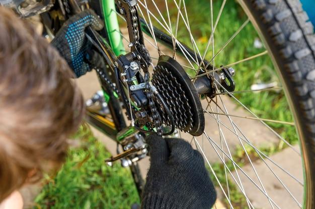 자전거 정비사는 자전거 수리점, 야외에서 자전거를 수리합니다. 자전거 타는 사람의 손이 현대적인 사이클 전송 시스템을 검사하고 수정합니다. 자전거 유지 관리, 스포츠 상점 개념입니다.