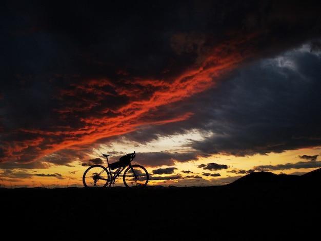 Велосипед на горе в красивом закате