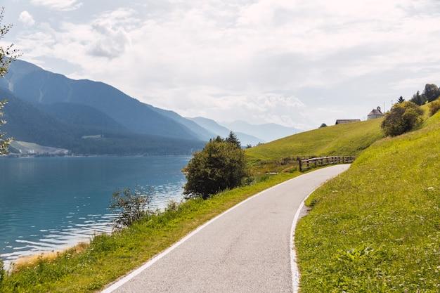 일부 흰 구름과 맑은 날에 이탈리아 알프스의 호수 주변 자전거 경로