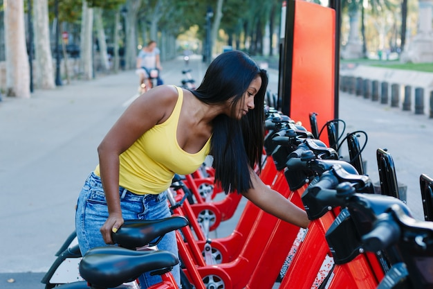 レンタサイクルサービス。自転車を1台借りる若い女性。生態学的輸送
