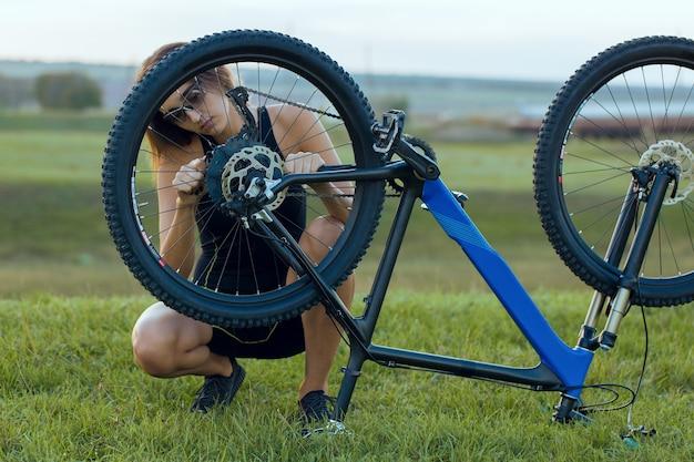 Bike repair. young girl repairing mountain bike on the green hills