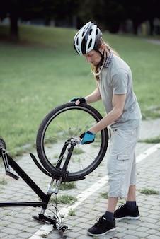 자전거 수리. 공원에서 산악 자전거를 수리하는 젊은 남자