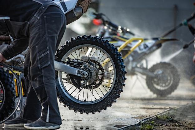 Велосипедист моет свой мотоцикл