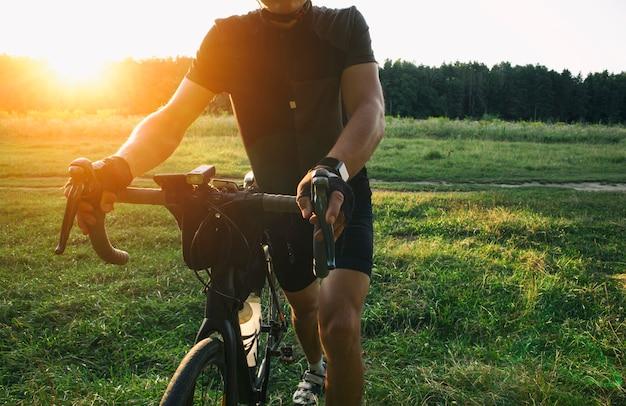 Велосипедист гуляет со своим велосипедом, набитым сумками, и ищет место для разбивки лагеря на закате