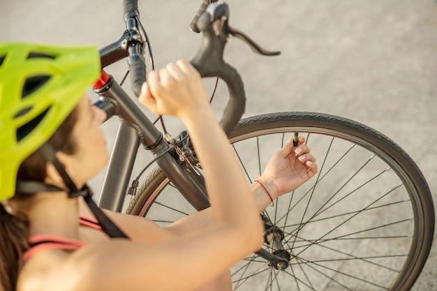 自転車のホイール。自転車のホイールを固定する明るいスポーツウェアの若いサイクリスト