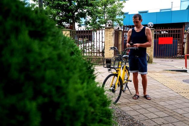 Bike yellow와 휴대폰. 도시의 거리와 공원에서 스마트폰으로 전자 차량 대여 서비스를 사용하는 남자. 젊은 남자는 여름에 친환경 교통수단을 빌린다.
