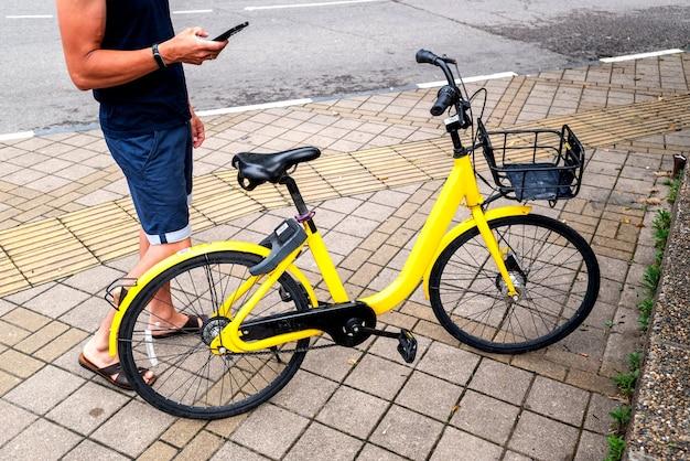 バイクイエローと携帯電話。都市の街路や公園でスマートフォンでe車のレンタルサービスを使用している男性。若い男は夏にエコ交通機関を借ります。