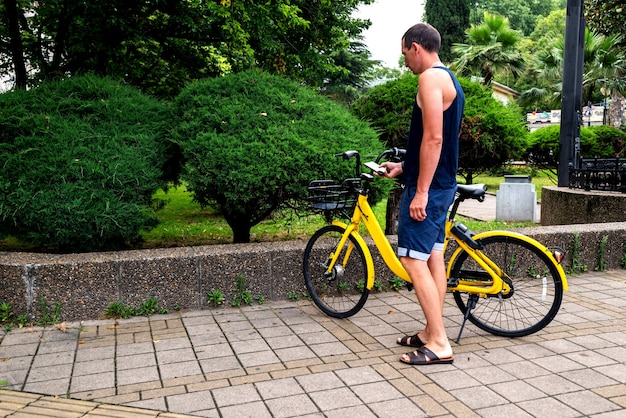 Bike yellow and mobile phone. man using e vehicle rent service with smartphone in urban city street and park. young man rent an eco transportation in summer.