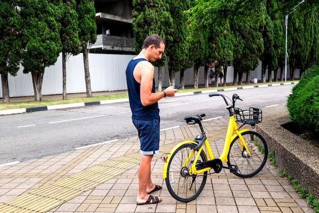 Bike yellow and mobile phone. man using e vehicle rent service with smartphone in urban city street and park. young man rent an eco transportation in summer