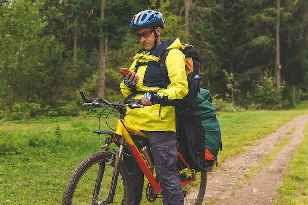 Bikepacker는 숲 한가운데에 서서 경로를 확인하는 스마트폰을 봅니다.