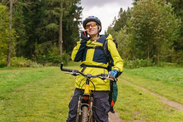 Bikepacker는 숲 한가운데 서서 전화 통화를 합니다.