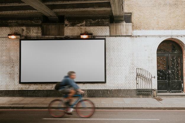 ロンドンの通りのデザインスペースで看板を通り過ぎて自転車に乗るバイカー