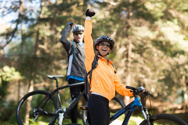 Biker couple clenching fist in forest