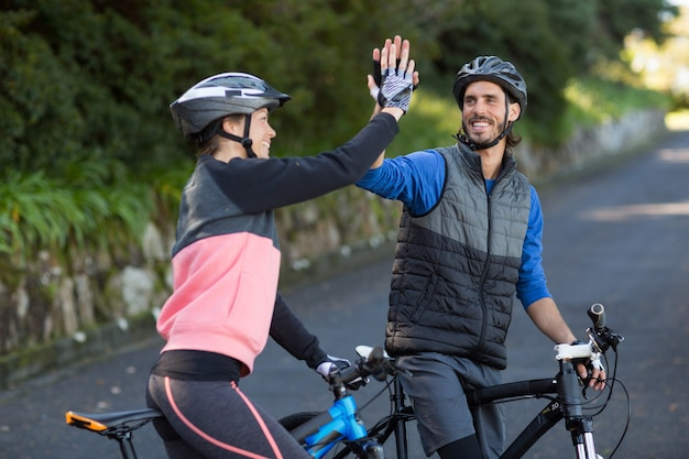 Байкер пара дает высокие пять во время езды на велосипеде по дороге