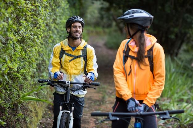 Байкер пара взаимодействует во время езды на велосипеде в сельской местности
