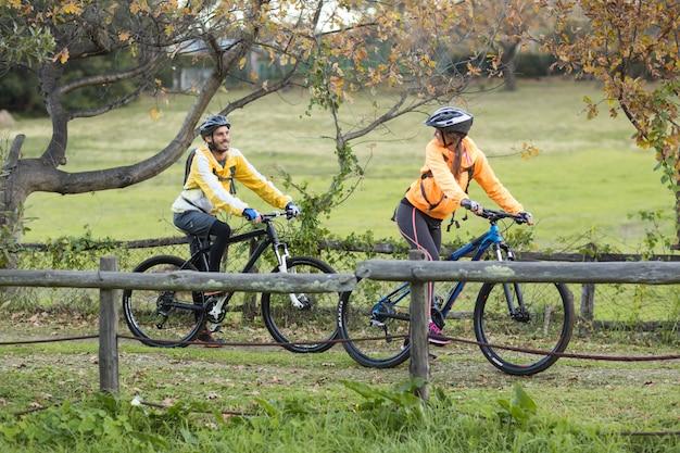Байкер пара взаимодействует во время езды на велосипеде