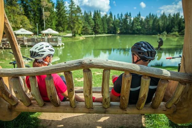 木製のブランコで休んでいるレイクブロークでのツアーのバイカーカップル 無料写真