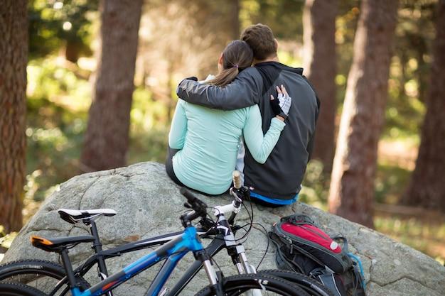 Biker couple sitting on rock in forest