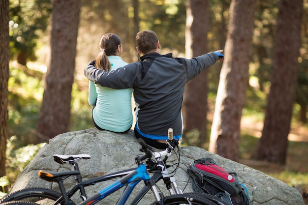 Biker couple sitting on rock pointing at distance in forest