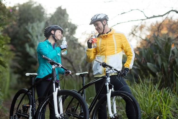 Байкер пара стоя с питьевой водой велосипедов в лесу