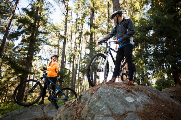 Biker couple standing with their mountain bike in forest