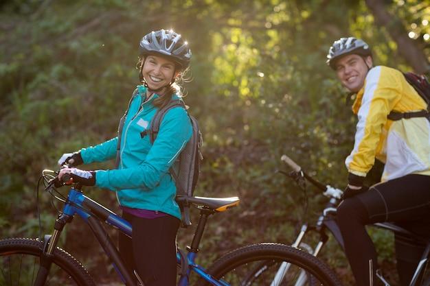 Байкер пара с горным велосипедом в сельской местности