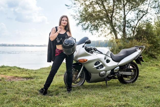 Biker girl holding leather jacket near motorcycle outside