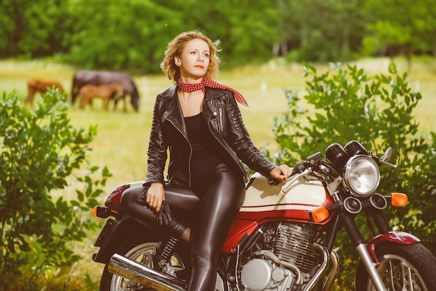 Biker girl in a leather jacket on a motorcycle against the background of horses.