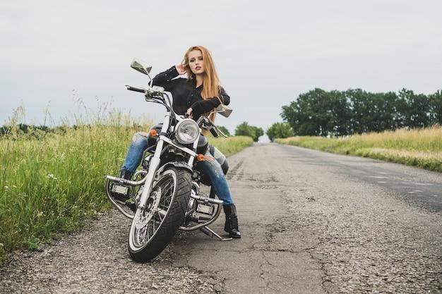 バイクでポーズをとるバイカーの女の子