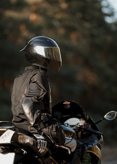 Байкер в шлеме и кожаном защитном снаряжении сидит на мотоцикле, спортивный быстрый мотоцикл