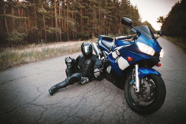 Байкер в защитном костюме и черном шлеме сидит рядом со своим мотоциклом на дороге. мотоциклист, отдыхающий возле мотоцикла