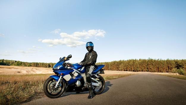 Байкер в черном на мотоцикле в кожаной куртке и шлеме
