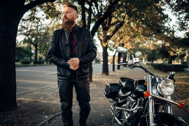 黒のチョッパーの近くの革のジャケットのバイカー