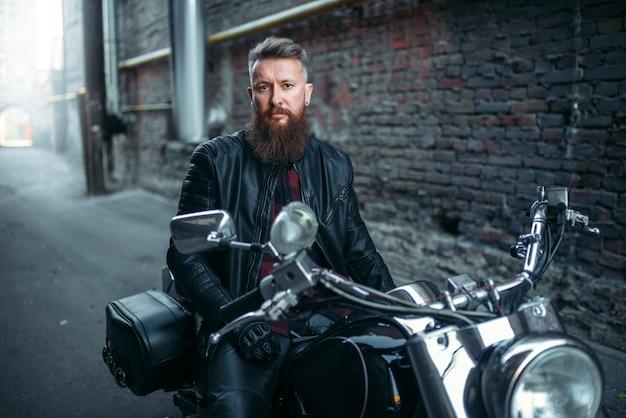 Байкер в кожаной куртке сидит на классическом чоппере. винтажный байк, всадник на мотоцикле, двухколесный транспорт