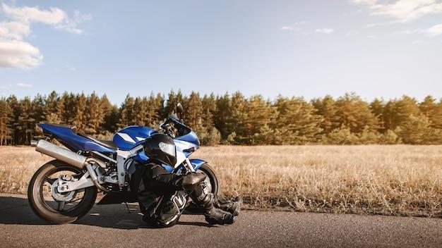 Байкер в кожаном костюме и черном шлеме сидит на асфальтовой дороге рядом со спортивным мотоциклом и смотрит вдаль.