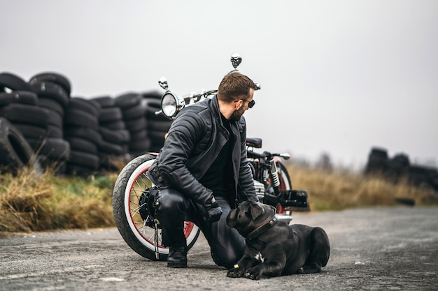 Biker in a leather suit crouched near his dog and red motorcycle on the road.