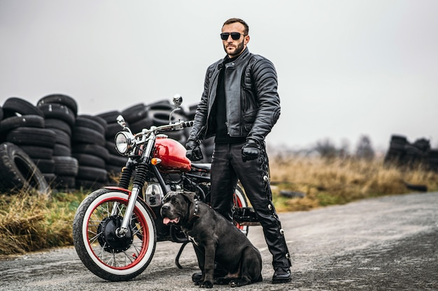 Biker in a leather suit and his dog stand near a red motorcycle on the road.
