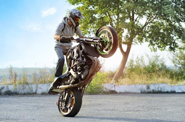 路上でスポーツバイクのトリックを作るバイカー