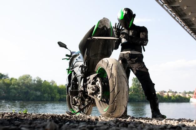 바이커 남자와 강 배경의 오토바이, 자유와 활동적인 라이프 스타일을 즐기는 강변의 거리에서 라이더 모토 여행. 엔듀로 여행 여행 컨셉