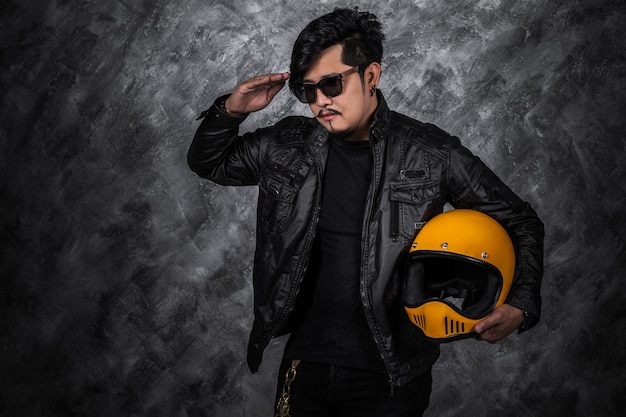 Biker man in black leather jacket saluting and holding helmet