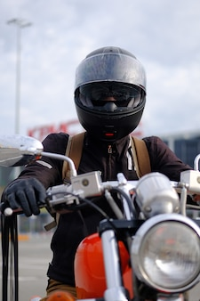 Biker man or guy-racer in a protective helmet sitting on a motorcycle .