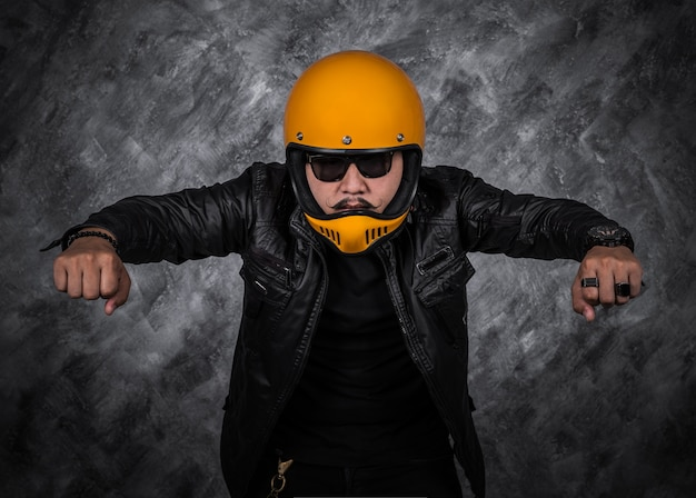Biker man in motorcycle helmet and black leather jacket